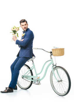stylish groom with wedding bouquet leaning on retro bicycle isolated on white