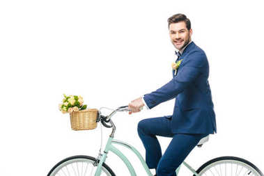 smiling groom in suit riding retro bicycle isolated on white