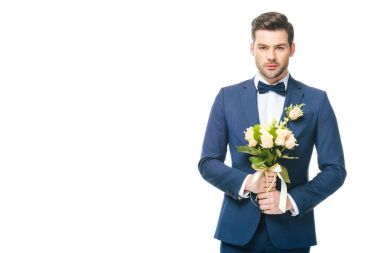 portrait of stylish groom in suit with wedding bouquet isolated on white