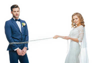 young bride holding groom on chain isolated on white
