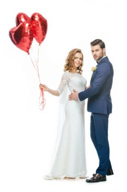 wedding couple with red heart shaped balloons isolated on white