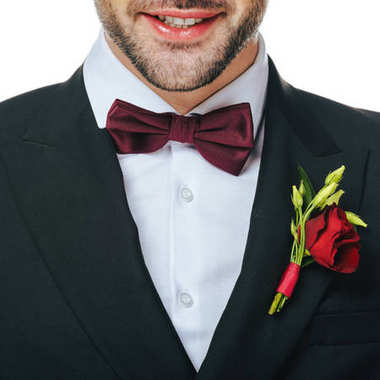 partial view of groom in suit with boutonniere isolated on white