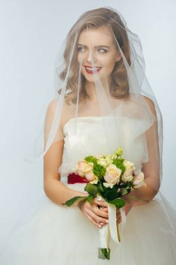 portrait of pretty bride in wedding dress and veil with wedding bouquet in hands
