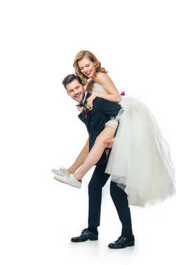 side view of groom and bride piggybacking together isolated on white