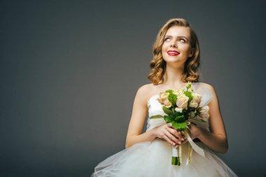 portrait of beautiful pensive bride with wedding bouquet looking away