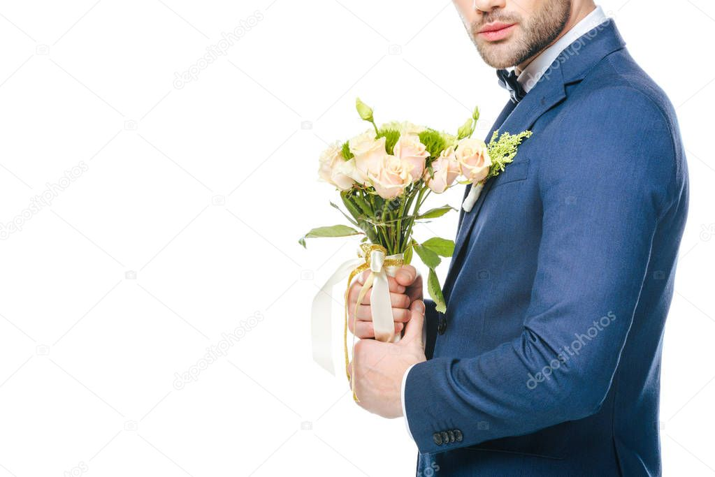 cropped sot of groom with bouquet of flowers isolated on white