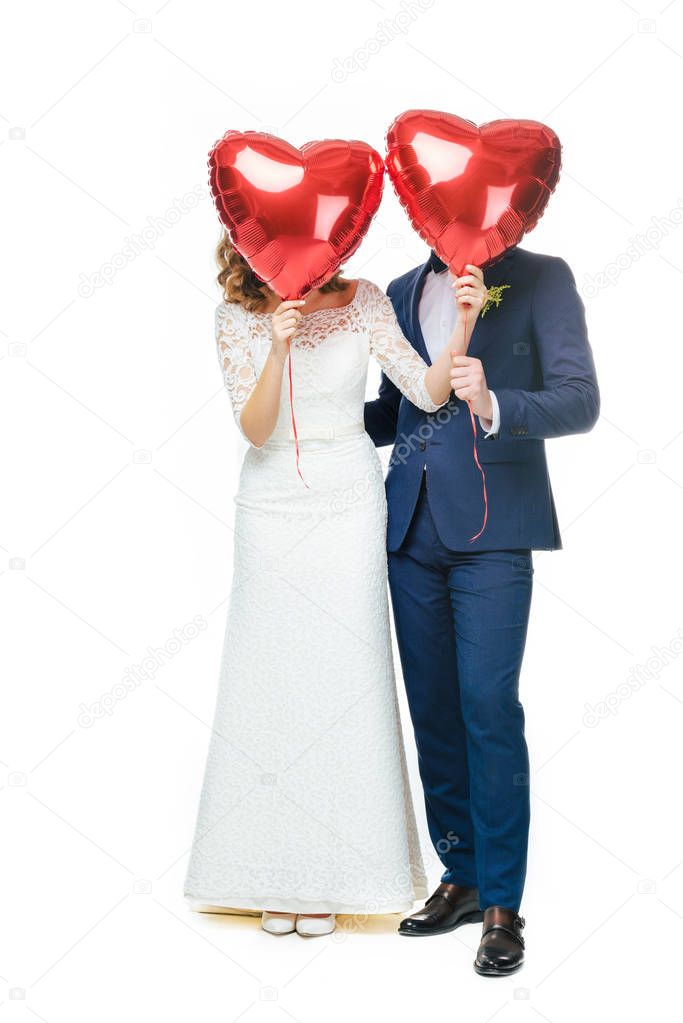 wedding couple covering faces with red heart shaped balloons isolated on white