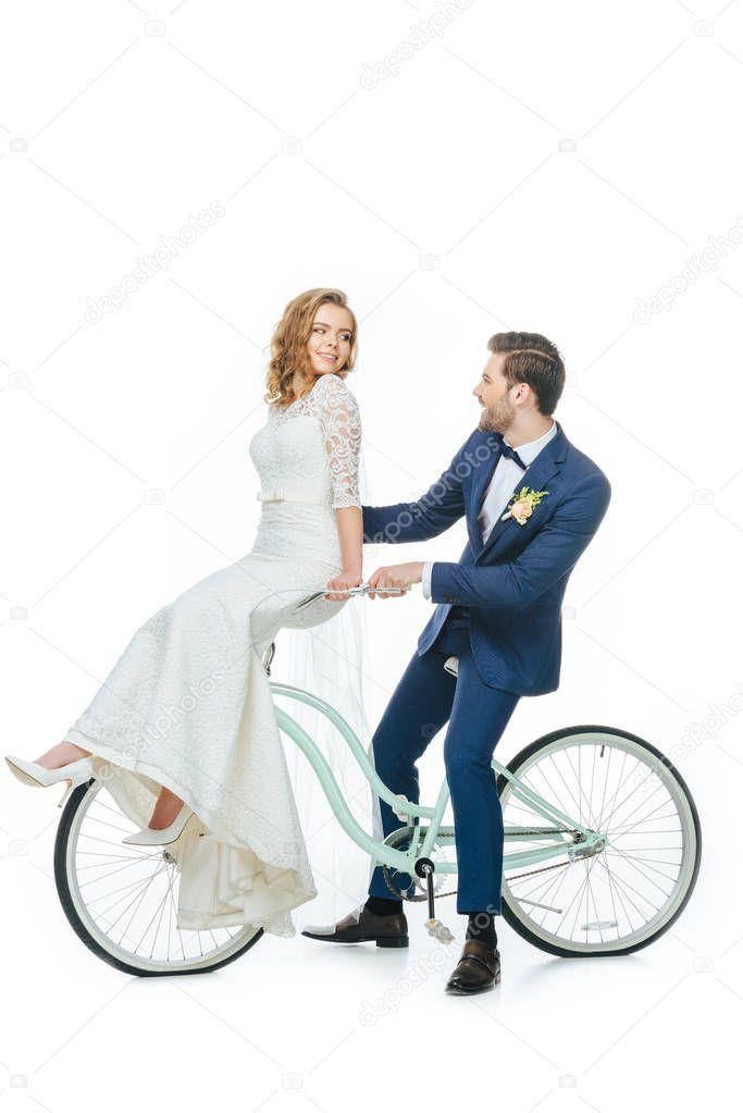 wedding couple riding retro bicycle isolated on white