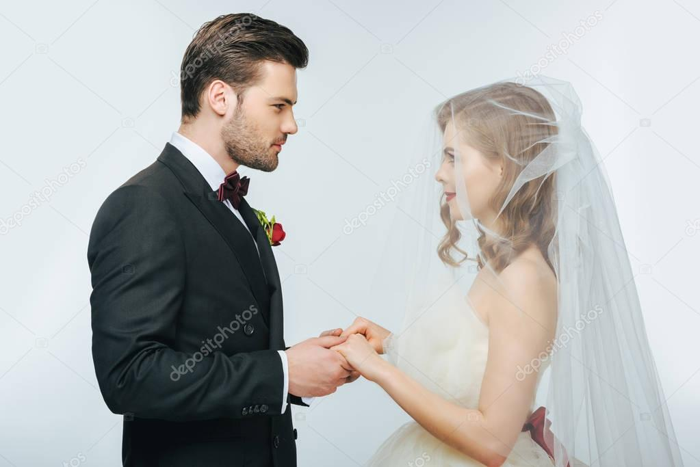 side view of beautiful wedding couple holding hands and looking at each other