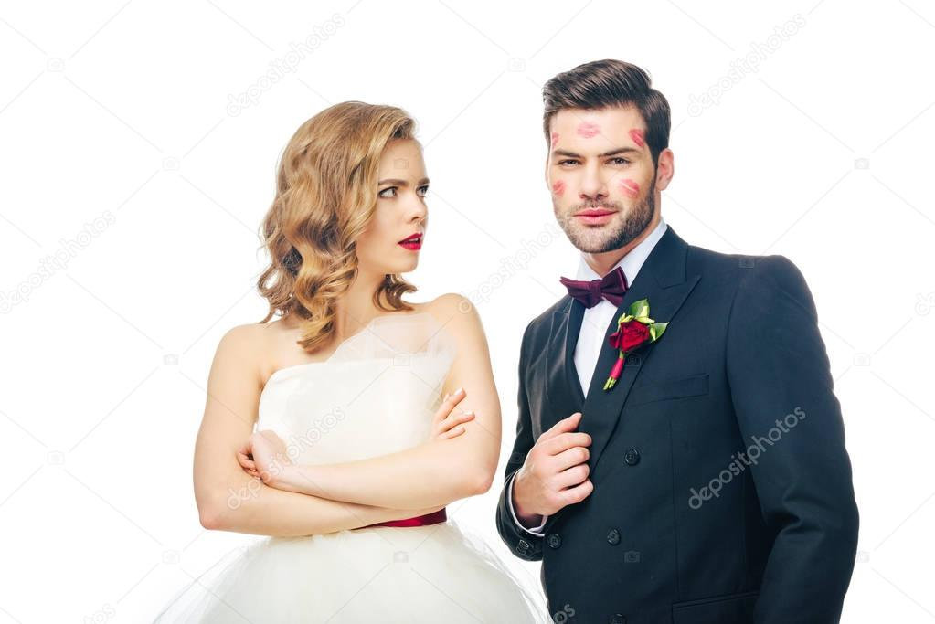 portrait of bride with arms crossed looking at groom with lipstick on face isolated on white