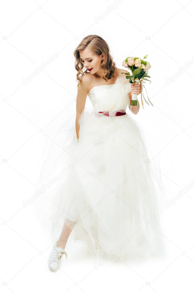 smiling bride in beautiful wedding dress with flowers in hand isolated on white