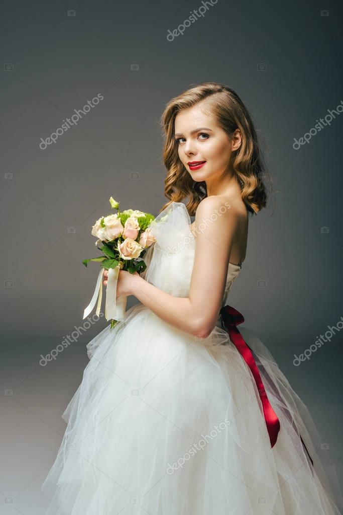side view of bride in wedding dress with bouquet of flowers