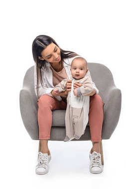 smiling young mother resting on arm chair together with little baby isolated on white