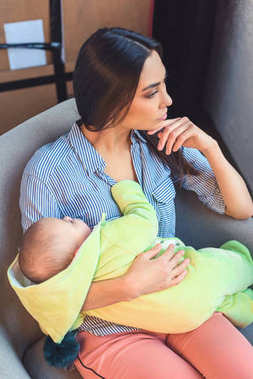 thoughtful mother with infant baby resting on arm chair at home