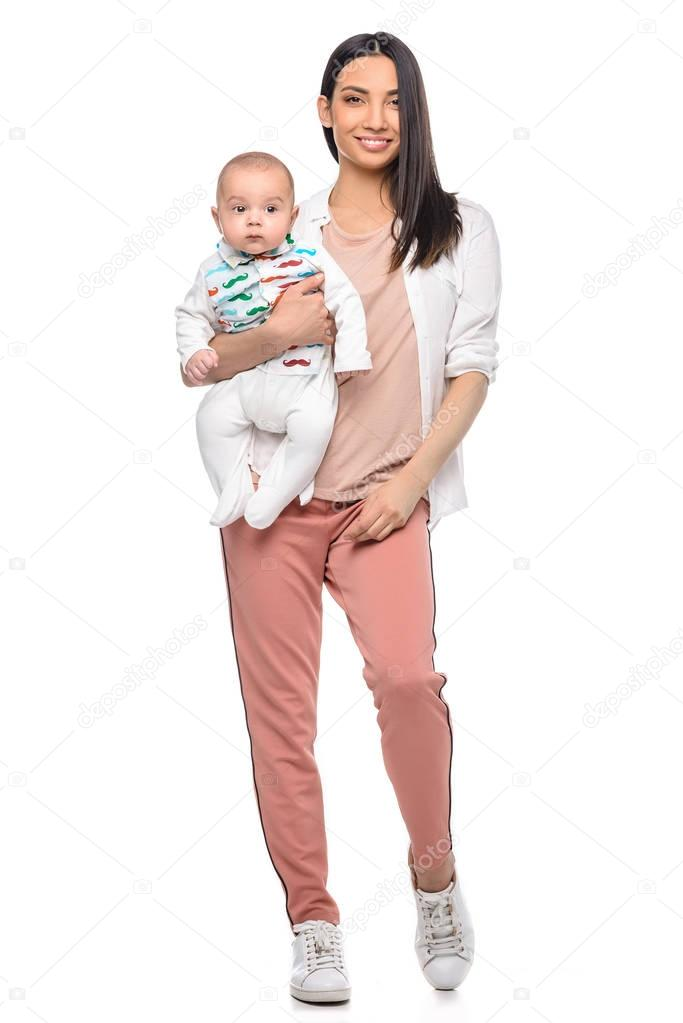 smiling woman with adorable baby in hand looking at camera isolated on white