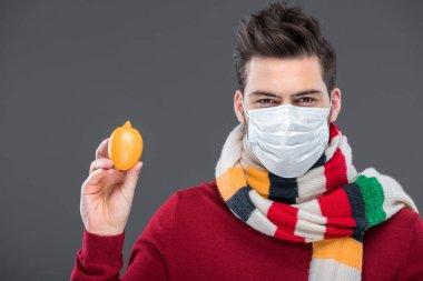 hasta adam sıcak eşarp ve tıbbi maskesi gri izole limon, holding