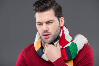 ill man coughing in warm scarf, isolated on grey