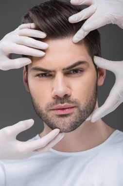 bearded man and doctors hands, isolated on grey, skin care concept
