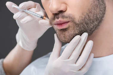 cropped view of hands in medical gloves making beauty injection for man, isolated on grey