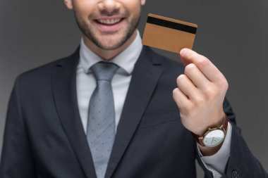 cropped view of businessman holding golden credit card, isolated on grey