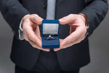 cropped view of man proposing with ring, isolated on grey