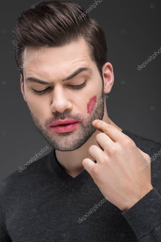 handsome bearded man with kiss print on cheek, isolated on grey