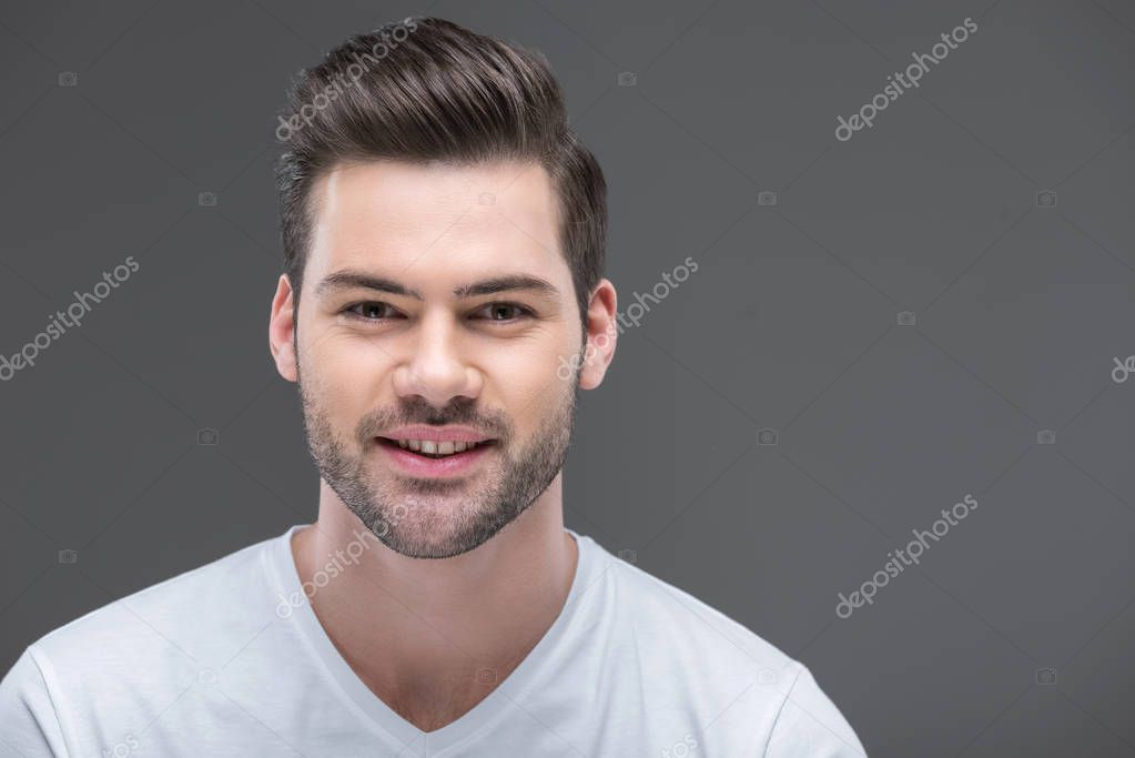 Portrait of handsome smiling bearded man, isolated on grey