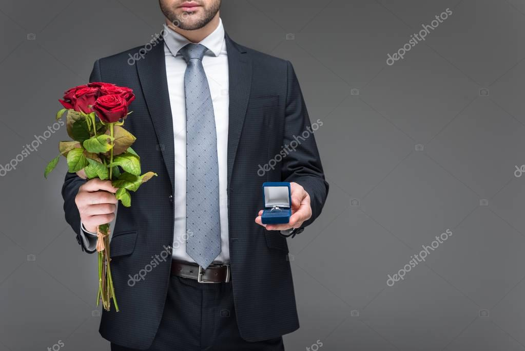 cropped view of man holding bouquet of red roses and proposal ring, isolated on grey
