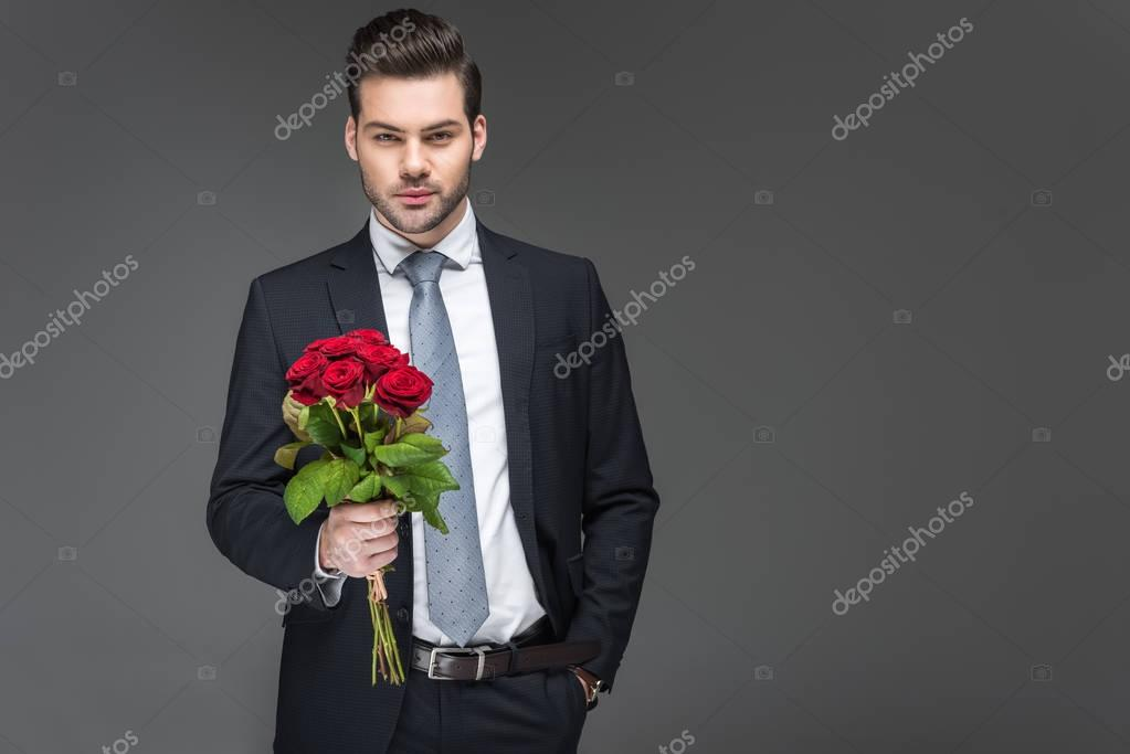 handsome man holding bouquet of red roses, isolated on grey