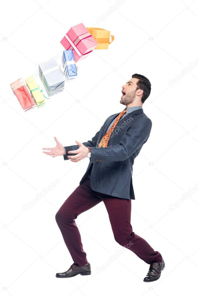 excited bearded man with falling gift boxes, isolated on white