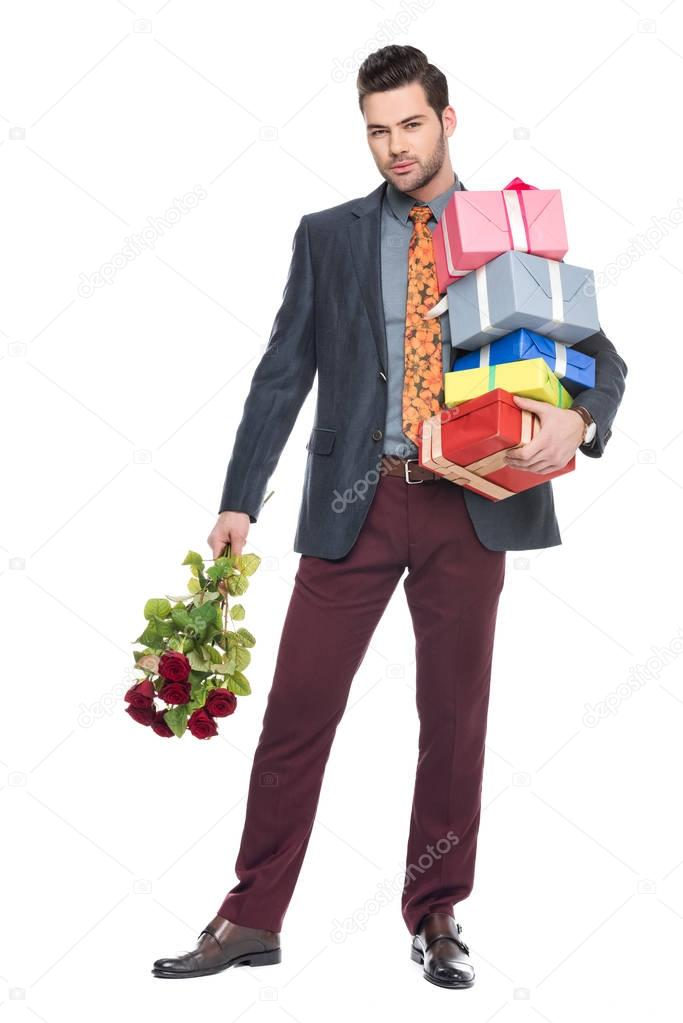 bearded man holding gift boxes and red roses, isolated on white