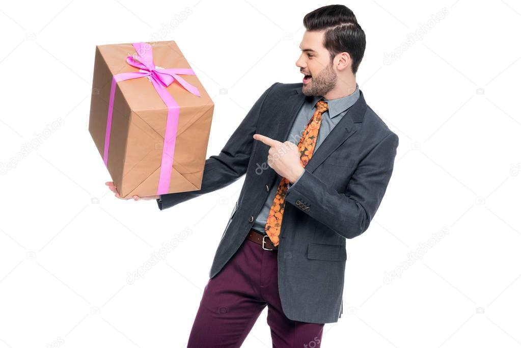 handsome excited man pointing at gift box, isolated on white