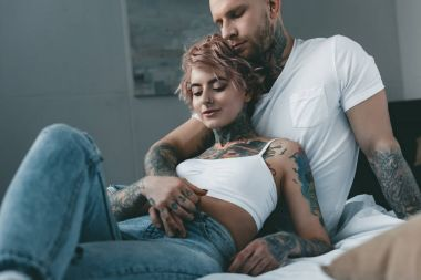 tender tattooed couple hugging, holding hands and lying on bed
