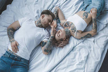 top view of tender tattooed lovers holding hands and relaxing on white bed