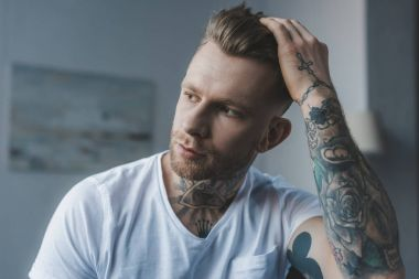 handsome stylish tattooed man touching his hair