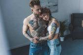 mladí tetovat, stylový pár objímat v ložnici