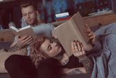 tattooed couple relaxing and reading books at home