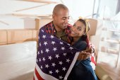 smiling african american couple hugging with usa flag