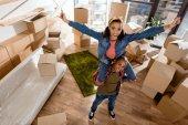 aufgeregtes afrikanisch-amerikanisches Mädchen sitzt auf den Schultern ihres Freundes und zieht in neue Wohnung