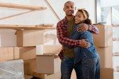 Fotografie šťastný pár afrických amerických objímání v novém bytě s kartony