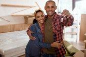 Fotografie šťastný pár afrických amerických drží klíče v novém bytě