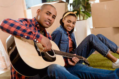 african american couple playing on acoustic guitar in new home with cardboard boxes