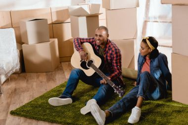 african american man playing on acoustic guitar for girlfriend in new apartment with cardboard boxes