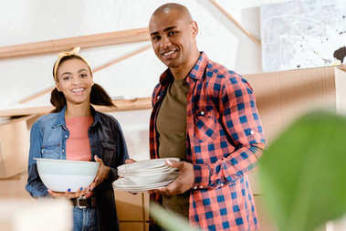 african american couple holding dishware in new home