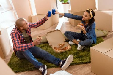 African american couple eating pizza and clinking with soda cans in new apartment with cardboard boxes stock vector