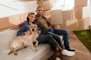 african american couple with labrador dog resting on sofa in new home