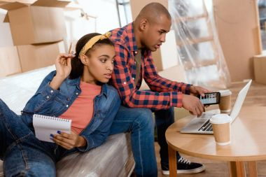 african american couple planning with notepad and gadgets on sofa in new home