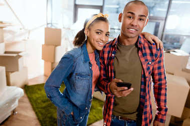 happy african american couple with smartphone in new apartment