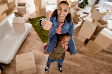 smiling african american girl sitting on shoulders of her boyfriend and showing thumb up in new home