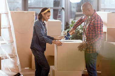 african american couple packing cardboard box to move in new apartment